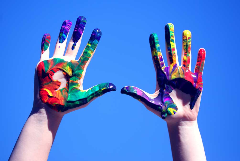 a child's hands with painted designs on them