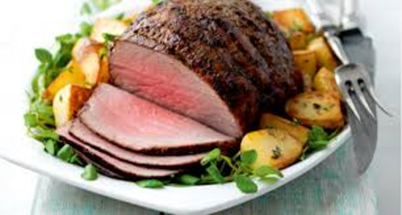carved roast beef on a plate with roast potatoes