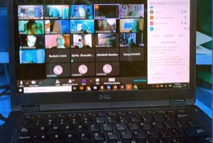 laptop with several people on screen in zoom meeting