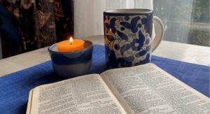 image of burning candle, mug of tea and an open bible