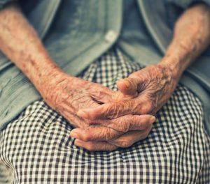 hands of old woman folded in her lap