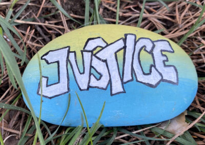 rock painted with the word Justice