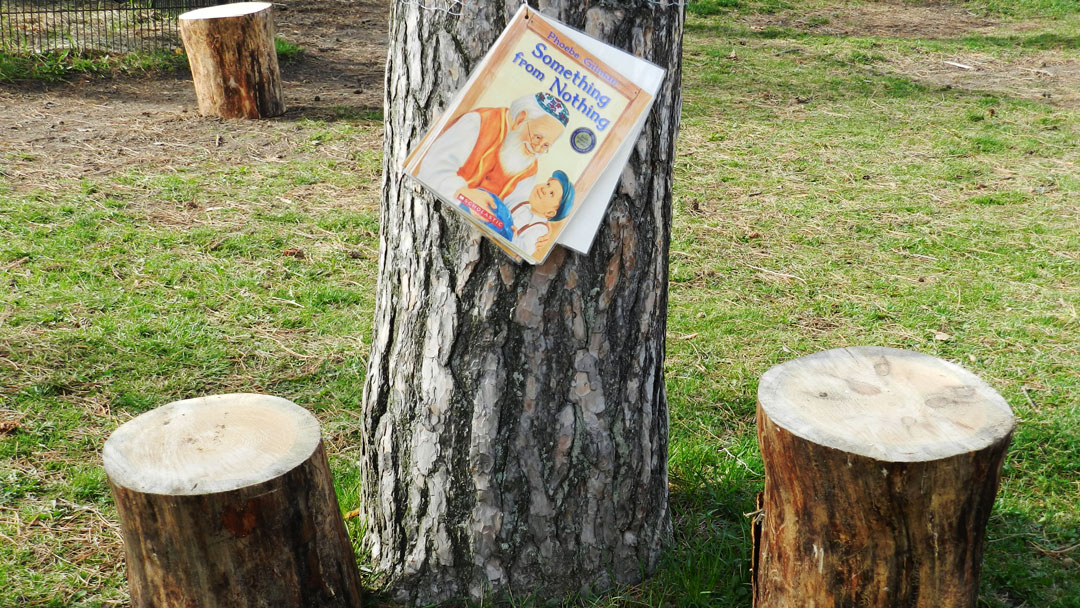 Something from Nothing book hanging from a tree with two stumps for seating in front