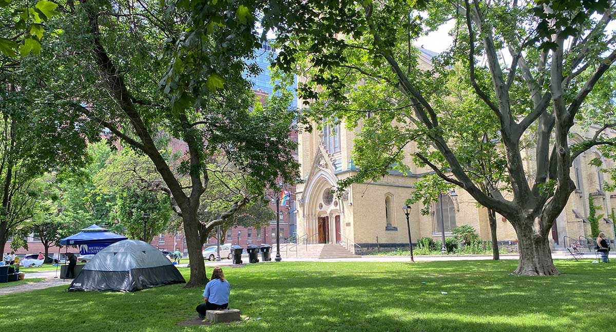 Person sitting on a stone on the grounds of Metropolitan United Church