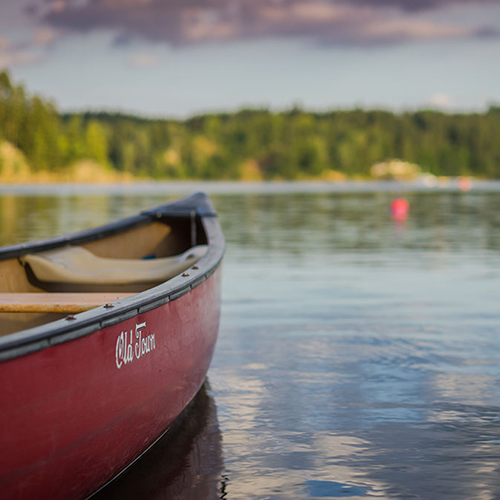 red canoe sitting in lake with shoreline