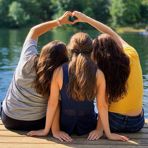 girls hugging on a dock